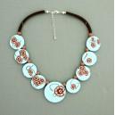 collier perles plates  fond turquoise clair fleur marron